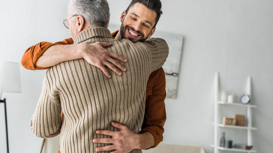happy bearded man smiling while hugging elder father at home